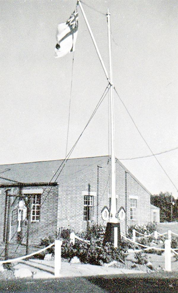 posing next to hms dauntless training establishment flag pole