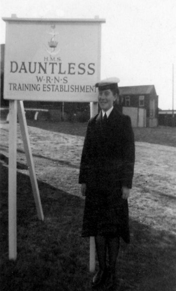 posing next to hms dauntless training establishment sign